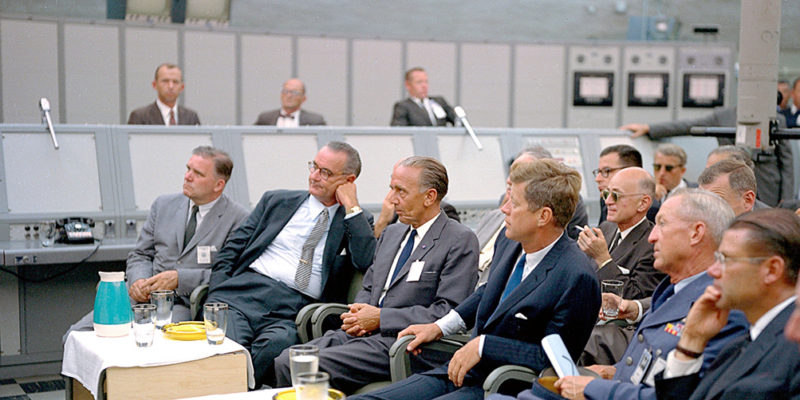 El presidente John F. Kennedy y el vicepresidente Lyndon B Johnson, durante una charla del director de lanzamientos de la NASA, Rocco Petrone (fuera de la imagen). Cabo Cañaveral, 11 de septiembre de 1962. Dominio público. NASA Commons.