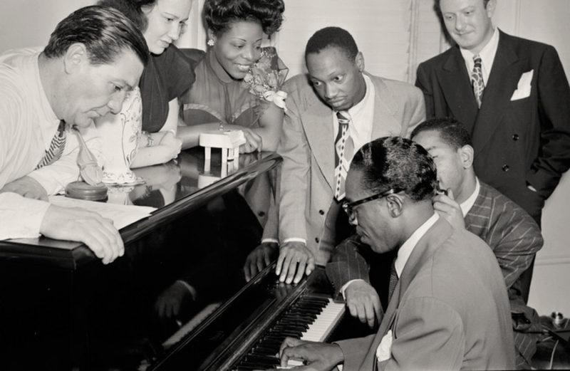 En la imagen, la compositora Mary Lou Williams (tercera desde la izquierda), el compositor Tadd Dameron (cuarto), junto a Hank Jones (al piano) y Dizzy Gillespie, en 1947. US Library of Congress. Colección William Gottlieb. Dominio público.